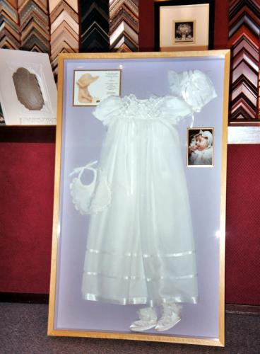 a large shadow box frame with christening dress
